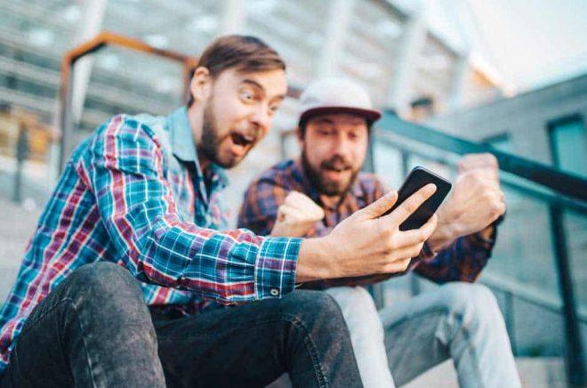 Johan och Johannes blev så här glada när Boktugg visade dem en lista på vilka uppläsare som tackat ja till Ljudboksfestivalen på Friends Arena. Foto: iStock.