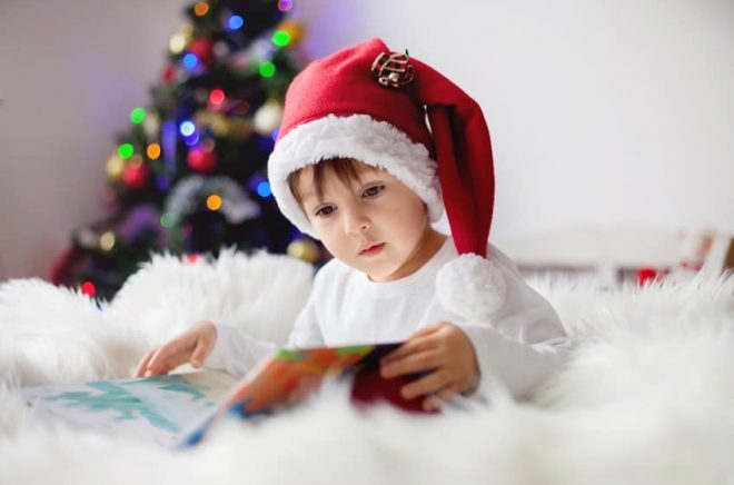 Cute adorable boy reading a book in front of the christmas tree
