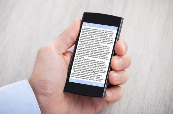 Businessman's Hand Displaying eBook On Smartphone