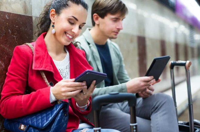 Subway passengers reading with modern gadgets as waiting the train
