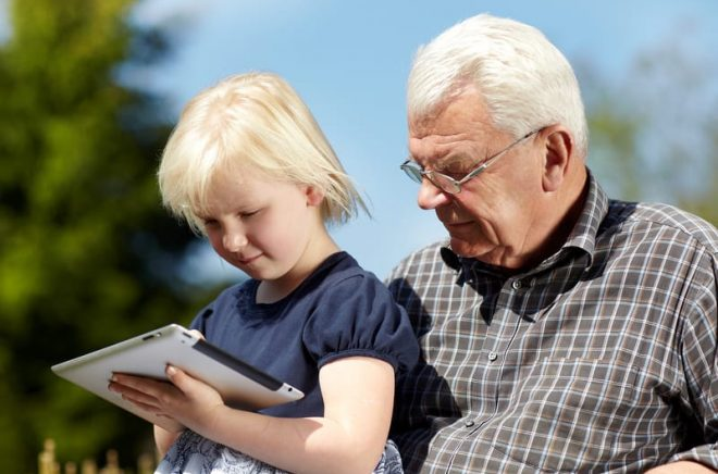 Old grandfather and little girl using touchpad e-book readers