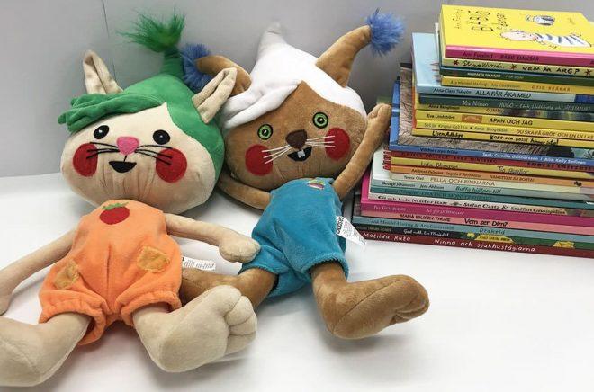 Bilderböcker som tävlar om att vinna Förskolebarnens litteraturpris, med maskotarna Poly och Glutt från bilderboksappen Polyglutt. Foto: ILT Inläsningstjänst