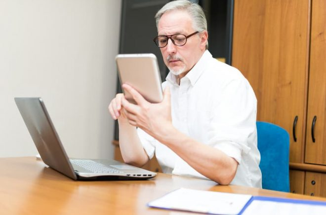 Man using a tablet and a laptop in his office