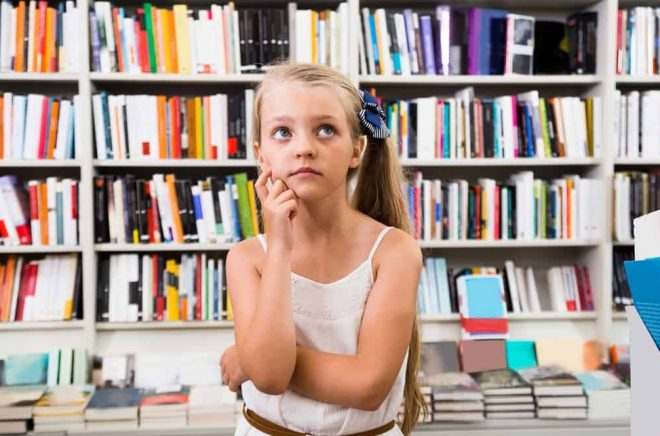 blond smart girl child bemused a lot of books in library