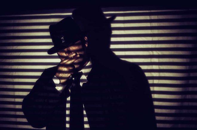 Film Noir Man Smoking Cigarette Shadows. Man in white shirt, black tie and hat standing smoking a cigarette in shadows of blinds, in film noir style.