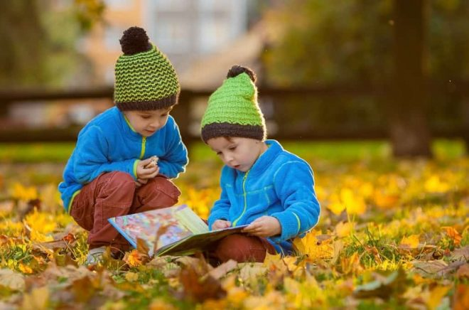 Two boys, reading a book on a lawn in the afternoon, eating snacks, autumn sunset time