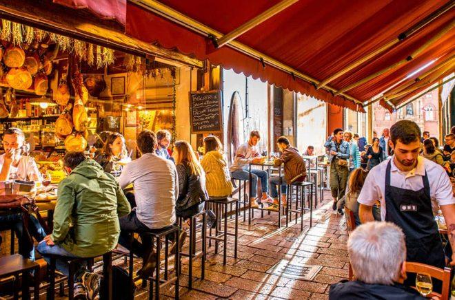 Bologna är en känt för sin gastronomi - och sin barnboksmässa. Här en uteservering i närheten på Pescherie Vecchie av matmarknaden i gamla stan. Foto: iStock. (Personerna på bilden har ingen koppling till artikeln)