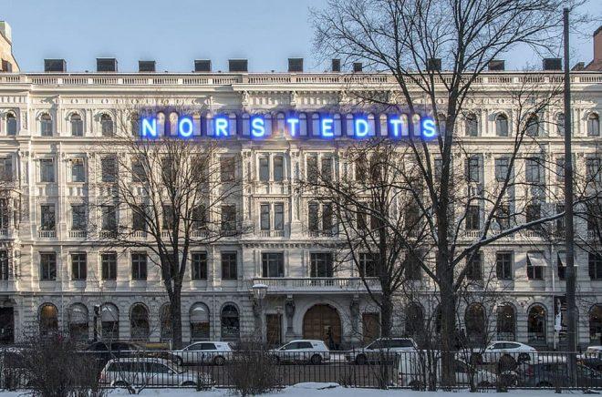 Norstedts köper Bonniers - aprilskämtet från 2015 och sätter upp sin klassiska logga på Bonnierhuset på Sveavägen 54-58. Foto Bonnierhuset: I99pema (CC BY-SA 3.0). Foto: Norstedtsloggan: Holger Ellgaard. Bilden är ett montage gjort av Boktugg.