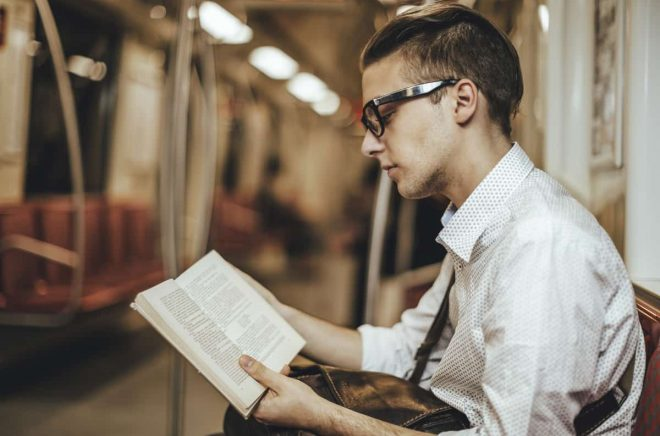Young man is reading a book on the underground. Candid shot.