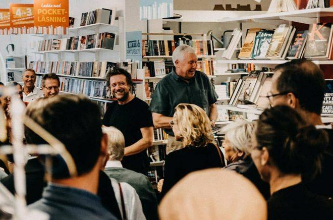 Fullsatt och festligt i Höganäs Bokhandel. Bokhandlaren (och förläggaren) Christoffer Palmer till vänster och författaren Lennart Rasmusson berättar om hur boken kom till. Foto: Conny Palmkvist.