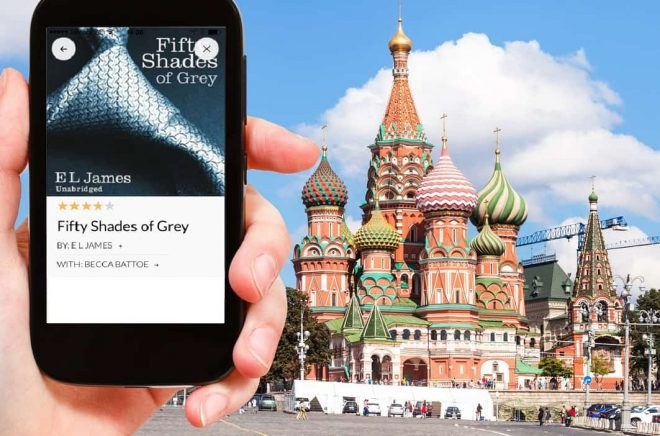 travel concept - hand holds smartphone with cut out screen and Saint Basil Cathedral on Moscoe Red Square on background
