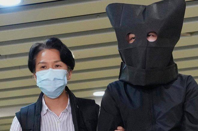 En misstänkt eskorteras av polis för att leta efter bevis på ett kontor i Hongkong den 22 juli. Polisen grep fem personer som misstänks ha förberett att sprida