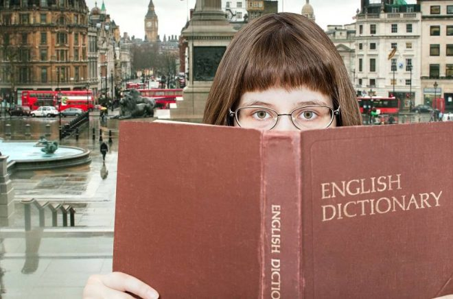 girl with spectacles looks over English Dictionary book and Trafalgar Square in London on background
