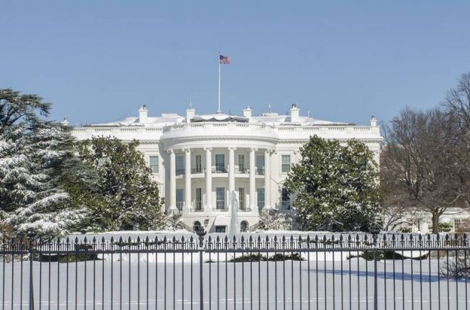 White House and grounds are covered with snow beneath a bright blue sky.