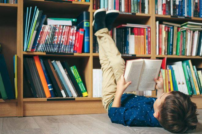 Läsande pojke på bibliotek. Foto: iStock.