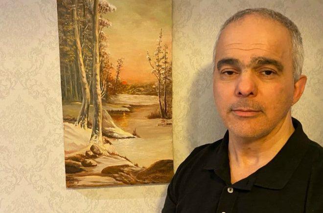Behroz Behnejad, taxichaufför och författare. Tavlan är målad av Behroz pappa. Foto: Privat
