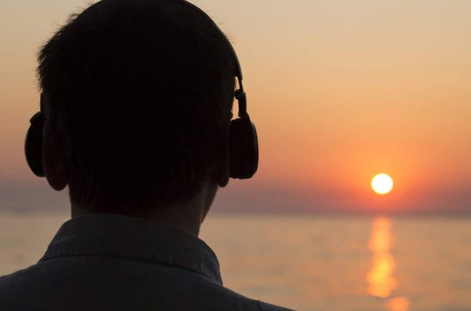 Young Man Is Watching Sunset While Listening Music