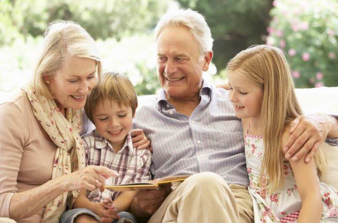 Portrait Of Grandparents Reading To Grandchildren On Sofa Smiling