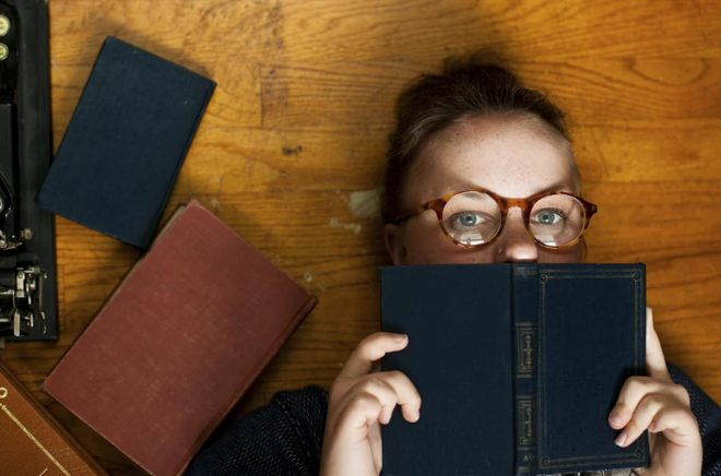 Horizontal portrait of a nerdy bookworm reading girl.