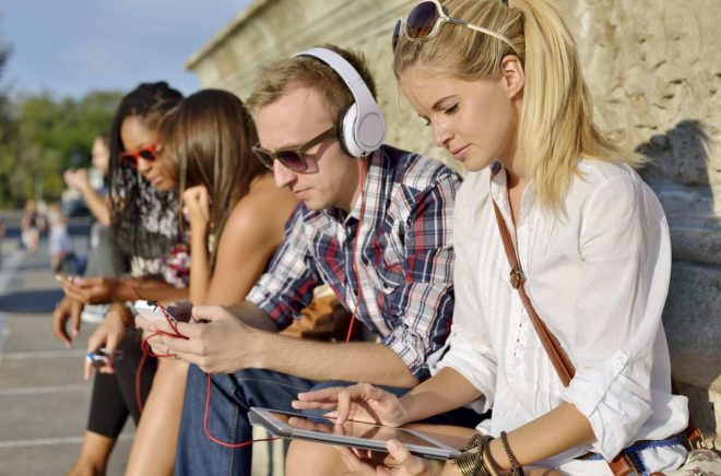 Young beautiful friends together outdoors, listening music, using tablet PC and smartphone.